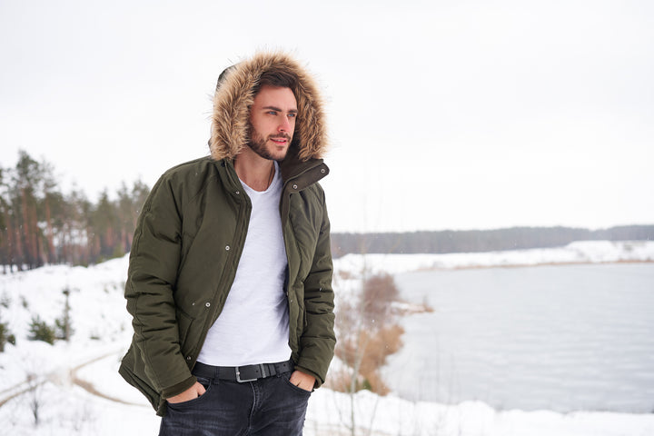 handsome young bearded man wearing fur lined parka walking in winter season forest
