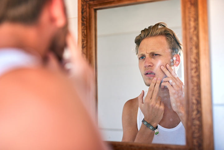 Handsome young man examining his skin in the mirror, looking for blackheads and spots