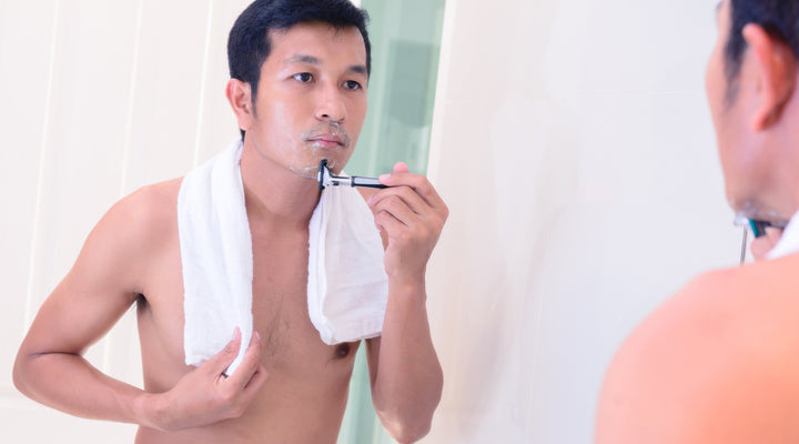handsome young man shaving sensitive skin looking in mirror with towel around neck