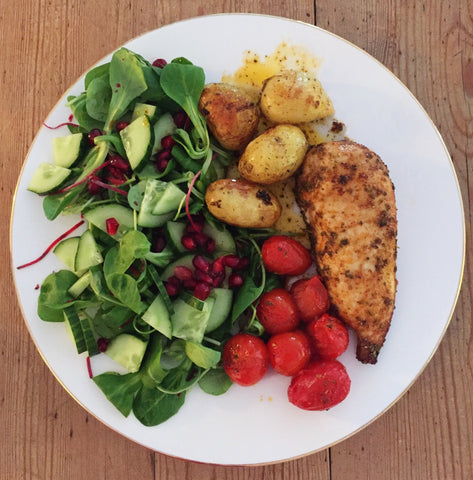 healthy foods on white plate - tomatoes, beets, salad, pomegranate seeds, chicken, sweet potatoes