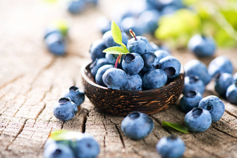 Freshly picked healthy blueberries in wooden bowl with green leaves on rustic table.
