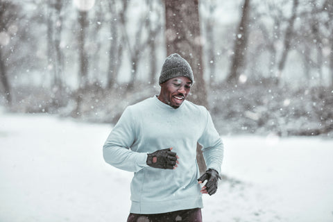 Handsome sporty black man running in the snow