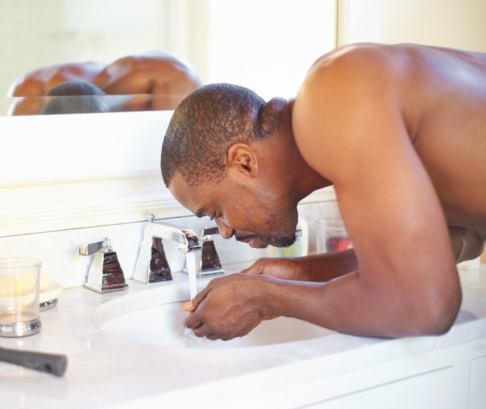 Handsome black man washing face at white sink with chrome taps