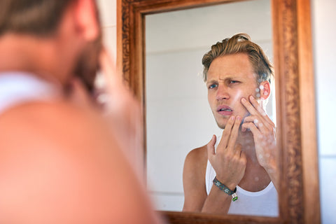handsome young man looking closely at his skin in the mirror