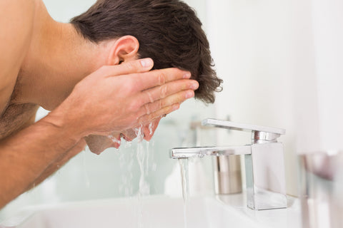 Handsome young man washing his face as part of daily skincare routine at white sink with chrome taps