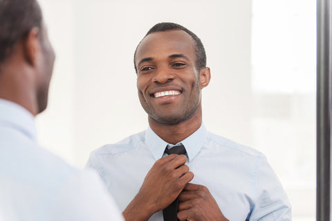 Handsome black man wearing white shirt looking in mirror and smiling