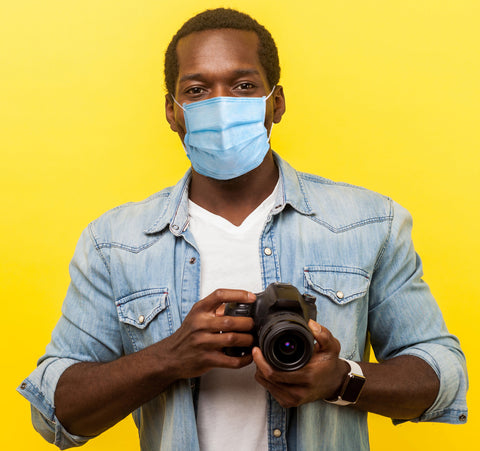 Handsome young black male photographer wearing a protective face mask holding a camera with yellow background