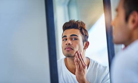 mens skincare routine man looking in mirror
