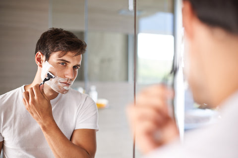 handsome young man shaving his face closely with razor