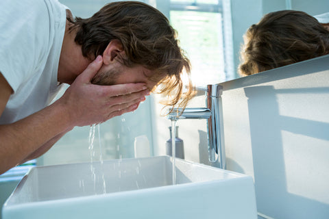 man with sensitive skin washing his face in white bathroom
