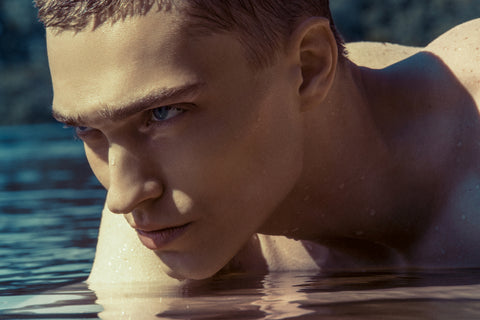 Handsome male model with oily skin in clear blue water