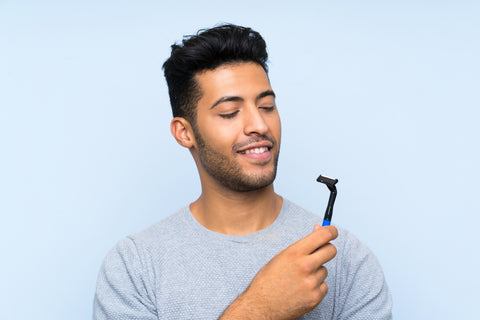 Handsome young man shaving his beard with happy expression