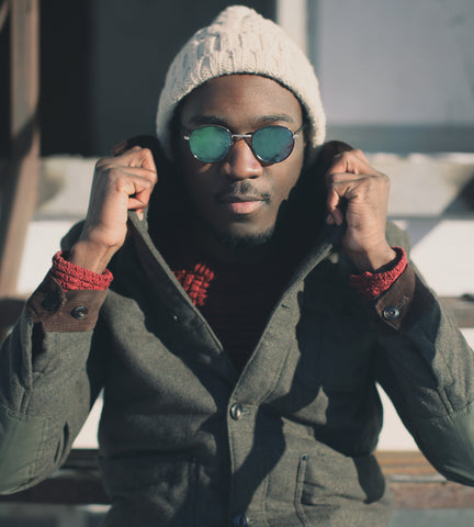 handsome young black man with cool sunglasses wrapped up warm against the winter cold
