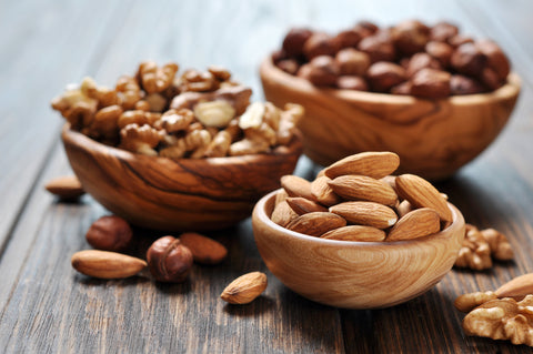 Almonds, walnuts and hazelnuts in wooden bowls