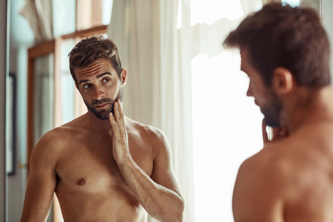 handsome young man looking in the mirror for signs of aging