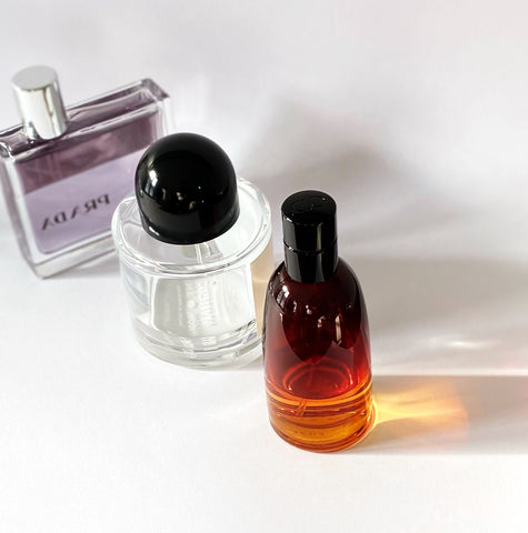Colognes that make you more attractive - glass bottles of men's cologne on white background
