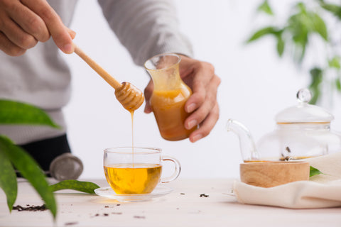 man pouring honey in to cup of green tea
