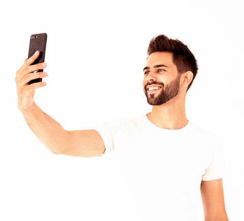 Handsome man smiling and taking a selfie photo