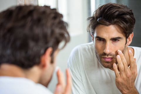 handsome man applying men's face cream looking in mirror