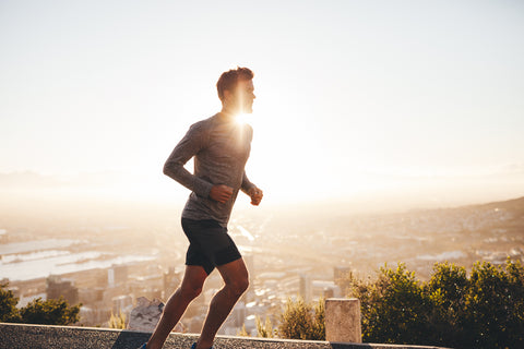 hansome young man running outside up a hill with sun in background