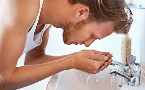 Handsome man washing his face, cupping his hands with water