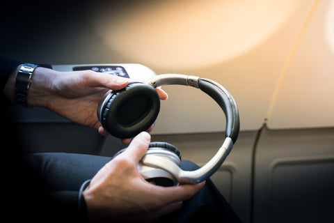 A passenger is holding noise-cancelling headphones of a business class cabin.