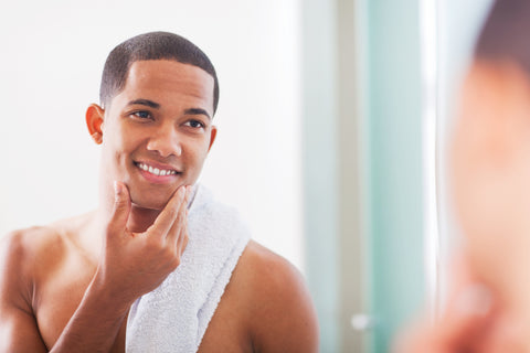 handsome man smiling feeling his smooth shaved face
