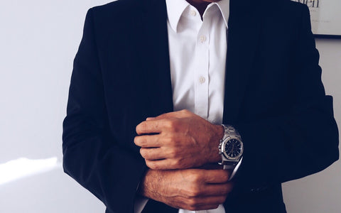 slim man wearing a dark navy suit with a white shirt and expensive watch