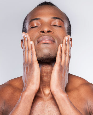Young black man smoothing his tight skin on his face with his hands
