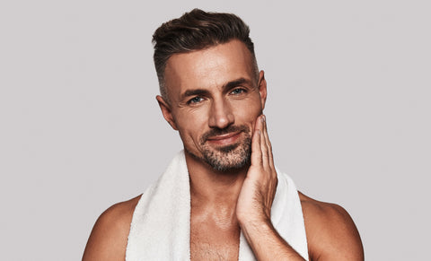 Confident in his skin. Handsome well-groomed young man applying moisturizer standing against grey background