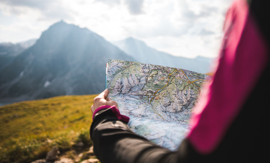 a person reviewing a map by a mountain range