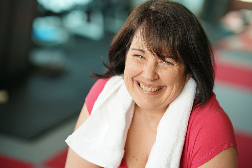 a smiling woman with a sweat towel sitting in a gym