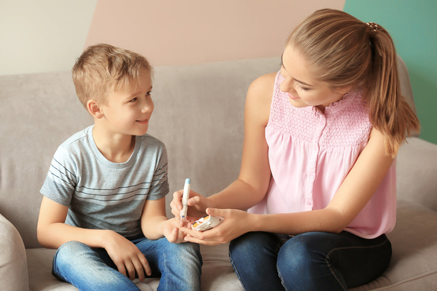 a woman helping her son take his blood sugar level