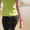 Woman walking wearing ROAD iD Red Pin Tuck Wrist ID