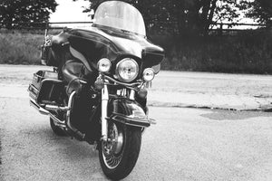 Black and white image of a parked motorcycle touring style with large wind fairing.