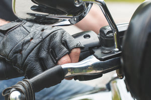 a hand in finger-less gloves grips the throttle of a motorcycle handle bar ready to give her some gas.
