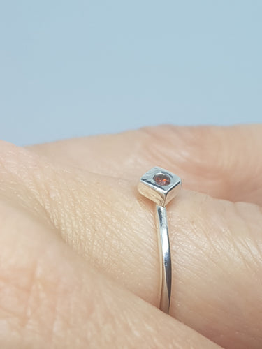 Sterling silver ring with a red cubic zirconia set in a cube