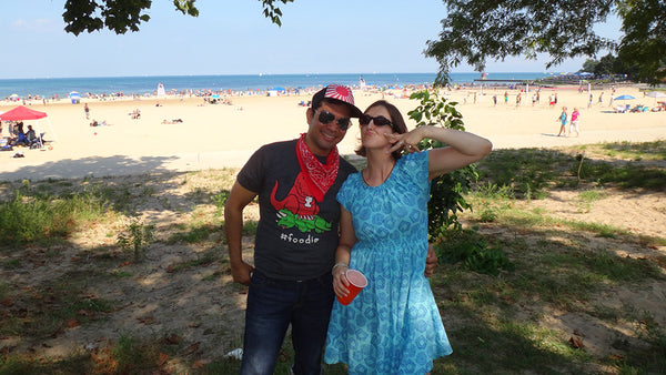 April wearing a short and patterned blue Mata dress next to her husband on a beach.