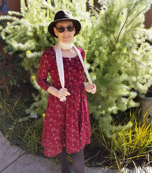 Deborah wearing a mid-length raspberry-colored printed Mata Traders dress with three-quarter sleeves, a fitted waistline, and a scoop neckline.