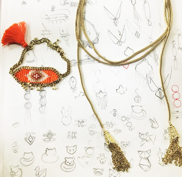 The Kira beaded bracelet and the Gia Rope necklace atop sketches of the jewelry.