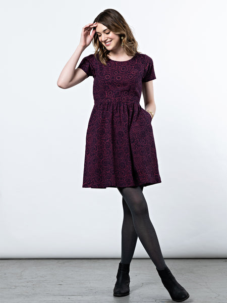 A model wearing the Paper Doll Dress in Magenta with black tights and black booties.