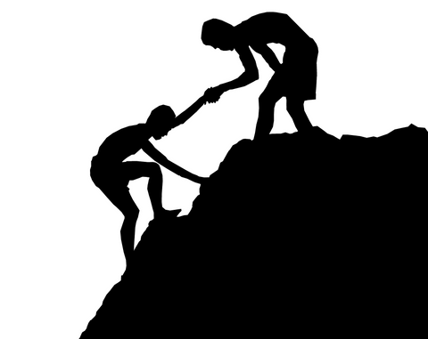 MAN HELPING ANOTHER MAN UP A MOUTAIN