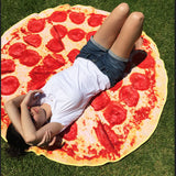 girl lying on pizza towel on grass