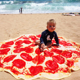 baby on pepperoni pizza towel on beach