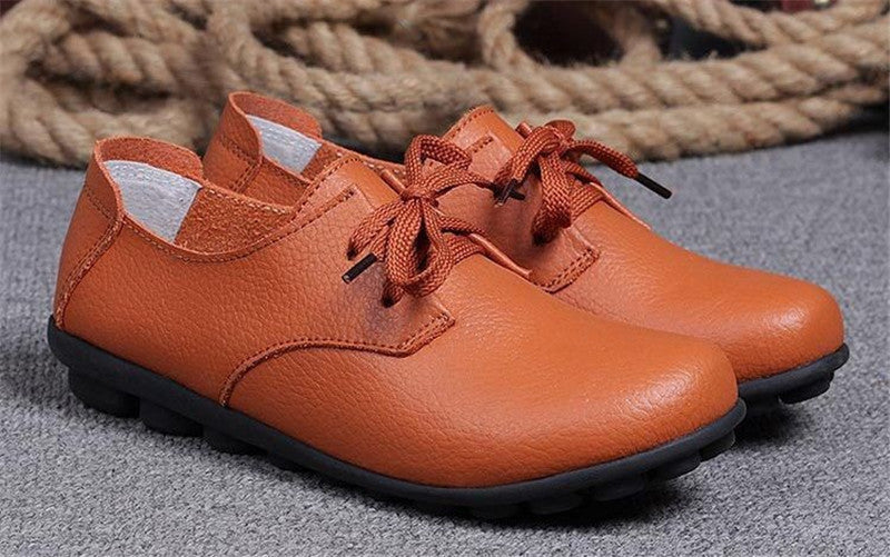 classic orange leather lace up comfortable womens shoes with black nodule soles near the nice rope