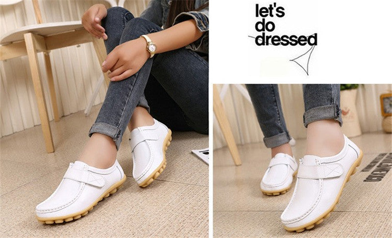 lovely white leather womens shoes with classic rubber sole nodules on a models feet wearing jeans
