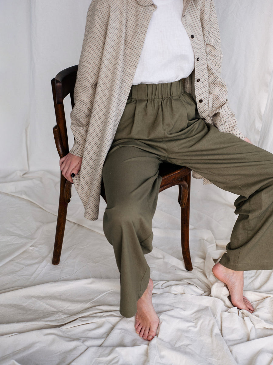 close up view, elasticated waist front pleated wide trousers of green forest linen