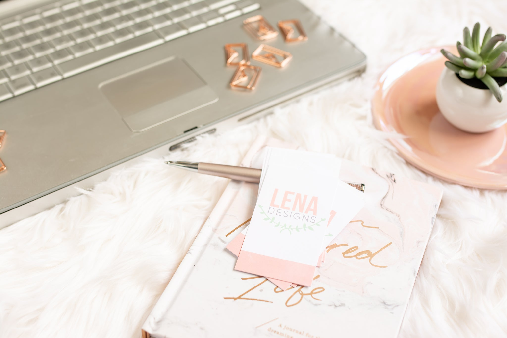 Lena Designs business cards in styled scene with laptop.