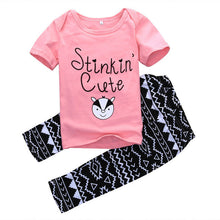 "Pink t-shirt with ""Stinkin Cute"" print and funky pants"