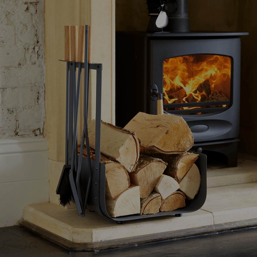 Valiant lifestyle image of Warwick log holder companion set filled with wood, on a hearth with stove roaring in fireplace